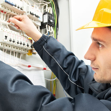 Marquette electrician working on industrial control panel