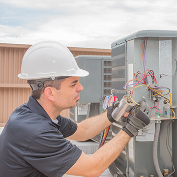 Marquette electrician repairing an AC unit